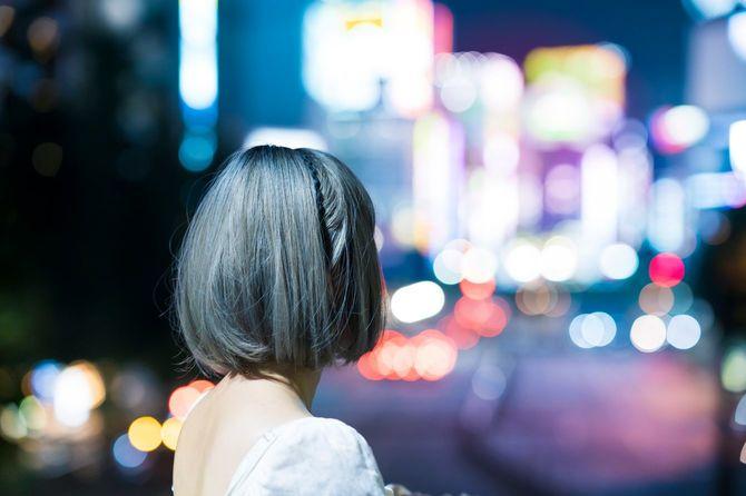 東京の輝く街並みを見つめる若い女性