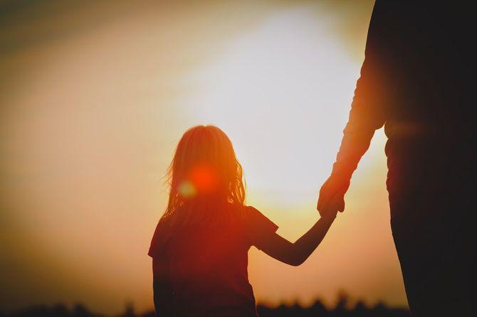 夕暮れ時に親の手を握る少女のシルエット