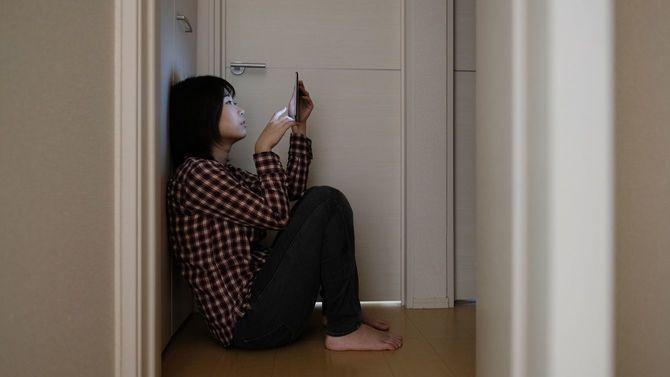 暗い部屋で床に座り込んでスマホをみる女性