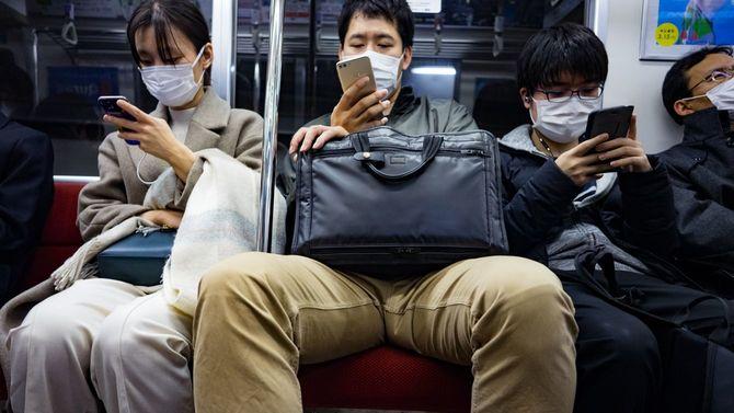 地下鉄でフェイスマスクを着用する通勤客たち