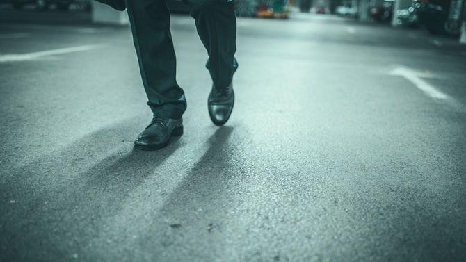 長い道のりを歩いて来てくたびれている男性の足元
