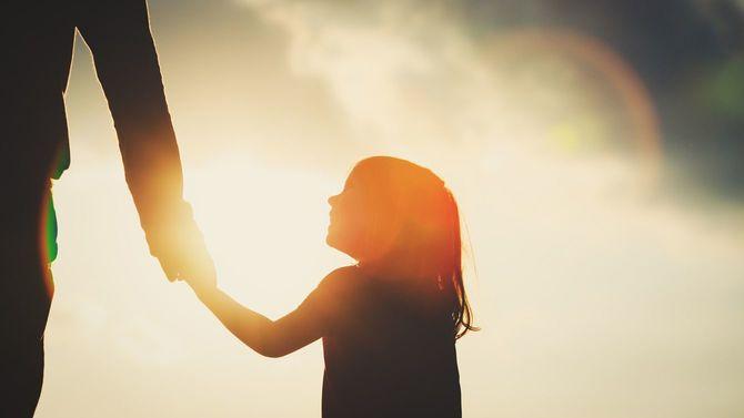 夕暮れ時に父親の手を握る少女のシルエット