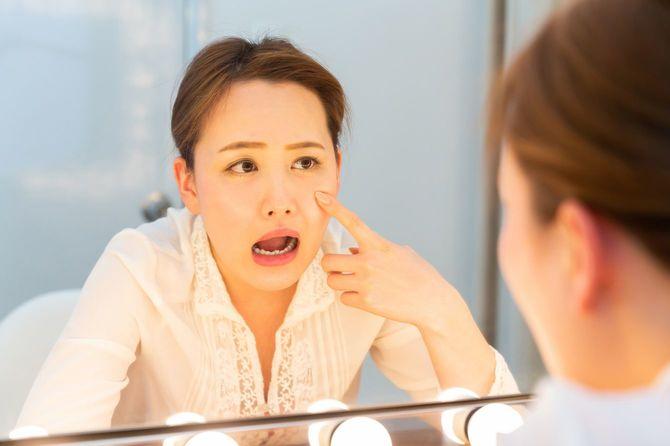 鏡をのぞき込む若い女性