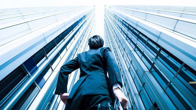 高層ビルを見上げる男性
