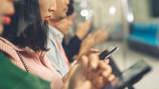 地下鉄で携帯電話を使用する若者たち