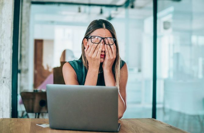 机に座って頭痛を伴う女性起業家