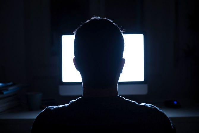 夜中にコンピューターのモニターの前に座っている人
