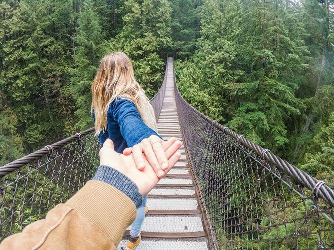 若い女性は吊り橋の上の森にボーイフレンドを導く