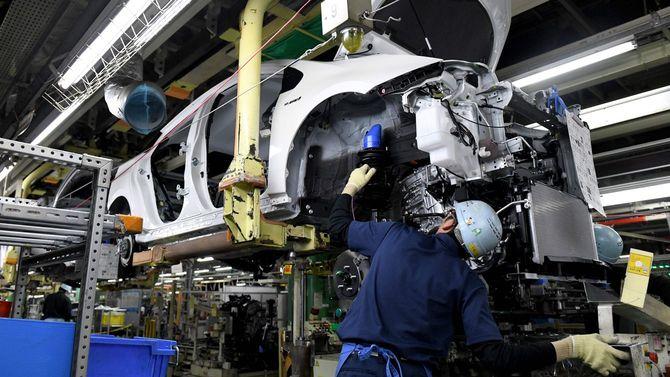 トヨタ自動車の堤工場(愛知県豊田市)の生産ラインで、4代目プリウスにエンジン部を組み付ける作業員たち=2017年12月8日