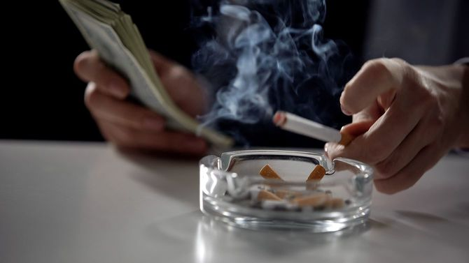 暗い部屋でタバコを吸いながら紙幣を数えるスーツの男性