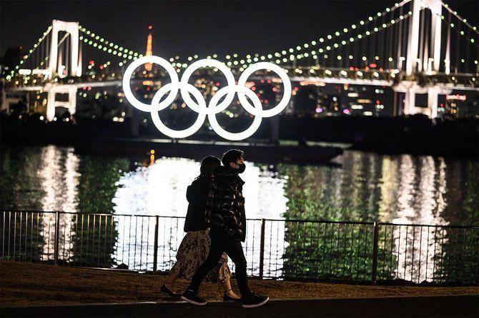 東京のお台場ウォーターフロントでオリンピックリングの前を歩く人々=2021年2月6日