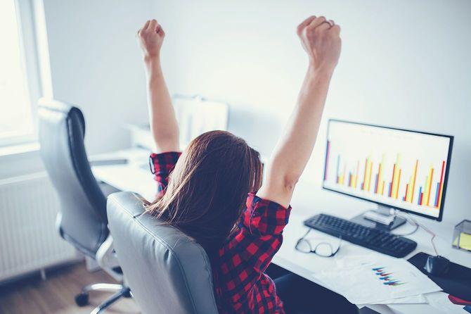 パソコンの前で両腕を上げる女性