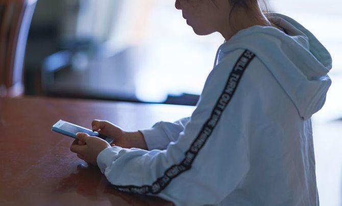 自宅の座卓でスマートフォンを見ている日本の女の子