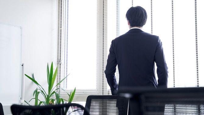 オフィスの窓の外を見ているビジネスマン