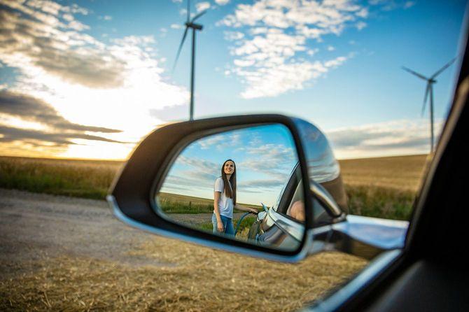 電気自動車を充電する女性が車のミラーに映る
