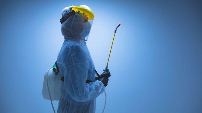 除染のための化学噴霧器を保持している科学者