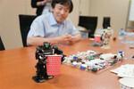 背丈が16.5cmのアイソボットに対し、紙コップは胸の高さ程度。ロボットの動く原理は、からくり人形とも共通点が。