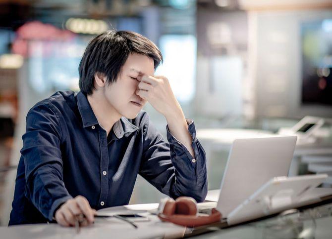 ラップトップで作業中、ストレスを感じて眉間をつまむ男性