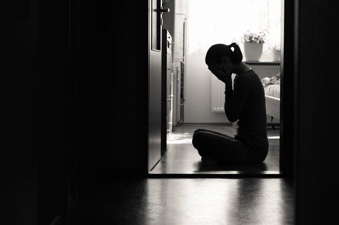 部屋の床に座り込んでいる悲痛な感情の女性