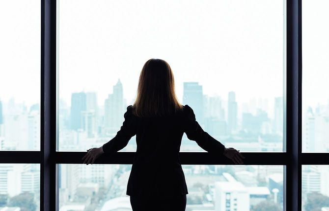 窓の外の都市をみる女性