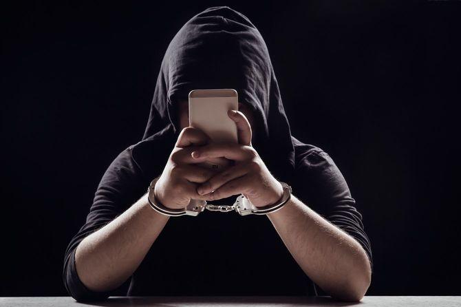 手錠をかけられたままスマートフォンを操作している黒い服の男