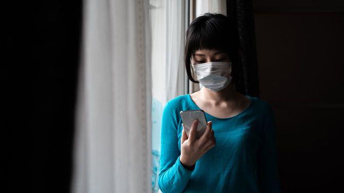 窓の近くでスマホをチェックする、マスクを着けた女性