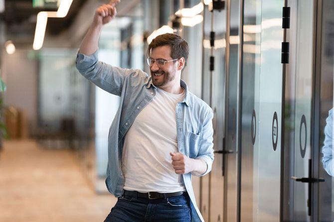 オフィスの廊下で喜ぶ男性