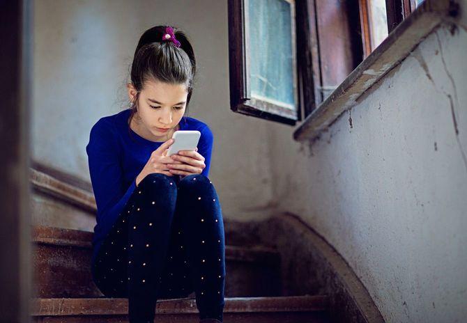 古い建物の階段でスマートフォンを見る女の子