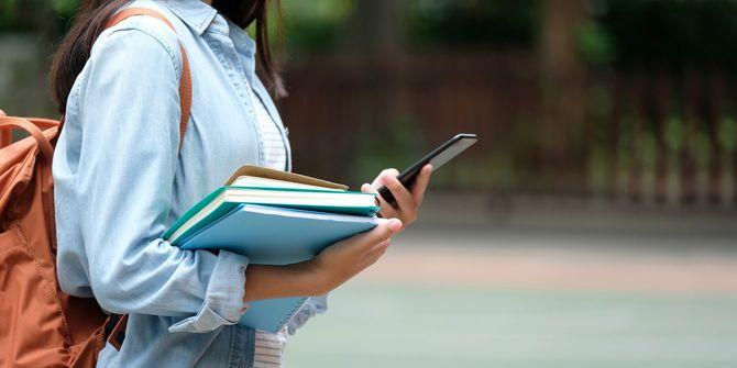 キャンパスでスマホを見ながら歩く女子学生