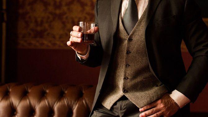 スタイリッシュな新郎がウイスキーの入ったグラスを手にしている
