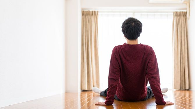 空っぽの部屋に座り込む男性