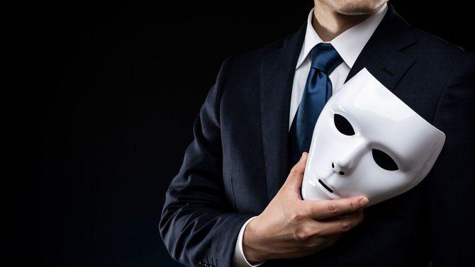 マスクを手にしたスーツの男性