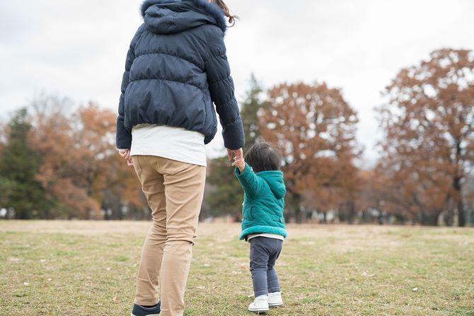 母親と息子が手を繋いで草の上を歩く