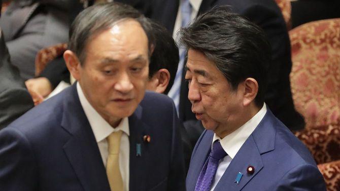 衆院予算委員会で答弁を終え、席へ戻る菅義偉官房長官(手前左)。右は安倍晋三首相=2020年2月5日、国会内