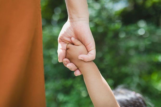 公園でお互いの手を握り合う母と娘