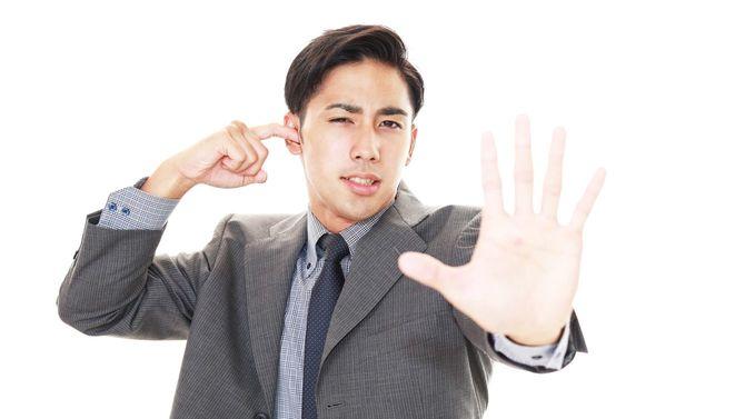 ストレスを感じるビジネスマンが片耳をふさいでいる
