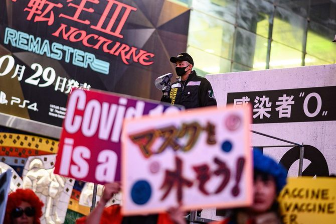 新型コロナウイルスの感染症対策などに抗議し、プラカードを掲げてデモをする人たち