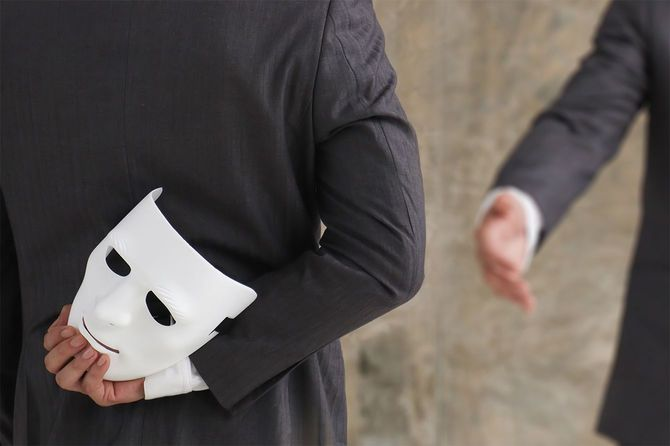 手に白いマスクを持つビジネスマン
