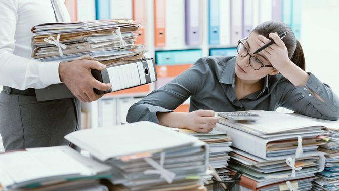上司が追加で運んできたファイルにストレスを感じる女性