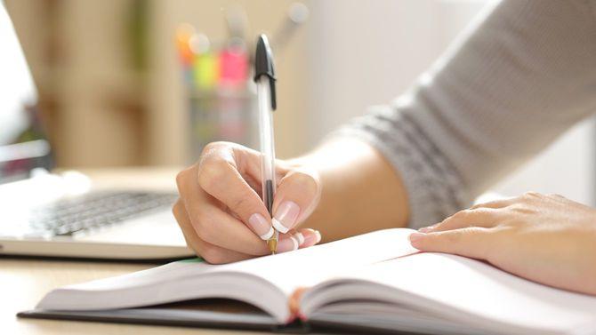 自宅の机で手帳に書き込む女性の手元