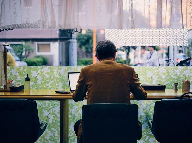 カフェでパソコンを開き仕事をする高齢男性