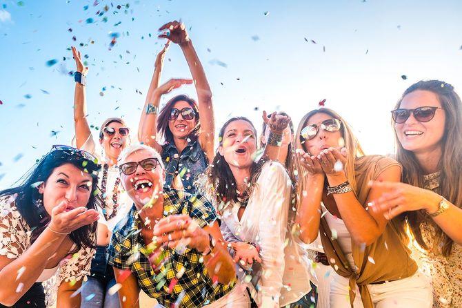 幸せな人々の陽気なグループは、お祝いのパーティーやカーニバルの間に一緒に楽しんでいる世代の女性を混合