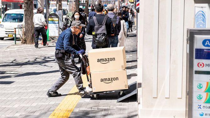 台車を押す高齢の配達員、新宿の街頭歩道でアマゾンの箱の荷物を届ける