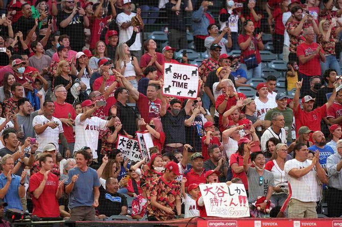 8月11日、大リーグのエンジェルス対ブルージェイズの試合で、3回裏の大谷翔平のホームランに歓喜するスタンドを埋めたファンたち。マスクをしている人はごく少数派。