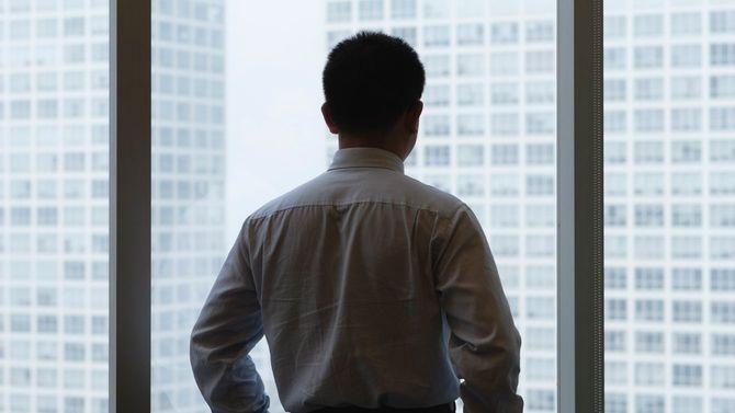 窓から外を見つめるビジネスパーソン