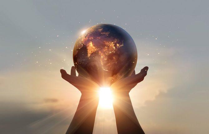地球を両手で持ち太陽に向かって掲げるグラフィック