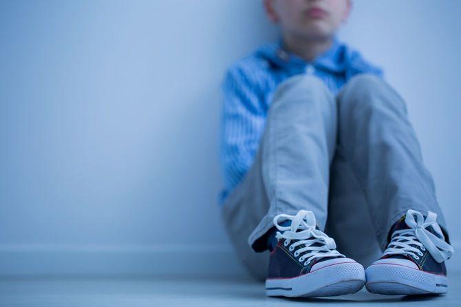 部屋に座り込んで悲しむ少年