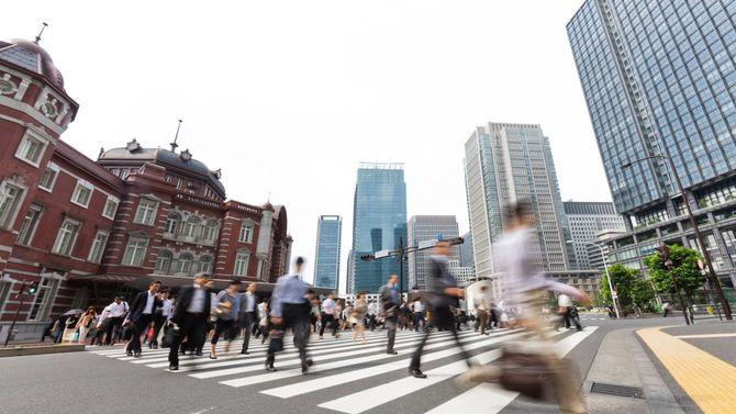 東京駅前の横断歩道を忙しく歩き去る人々