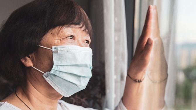マスクを着用し、窓から外を見ている年配女性