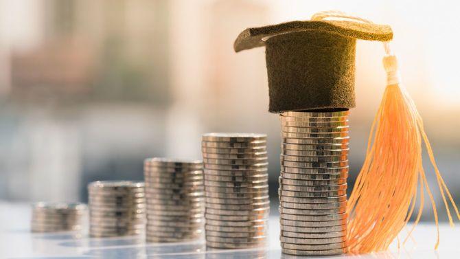 一番高く積み上げられたコインに学位帽がかぶせられている